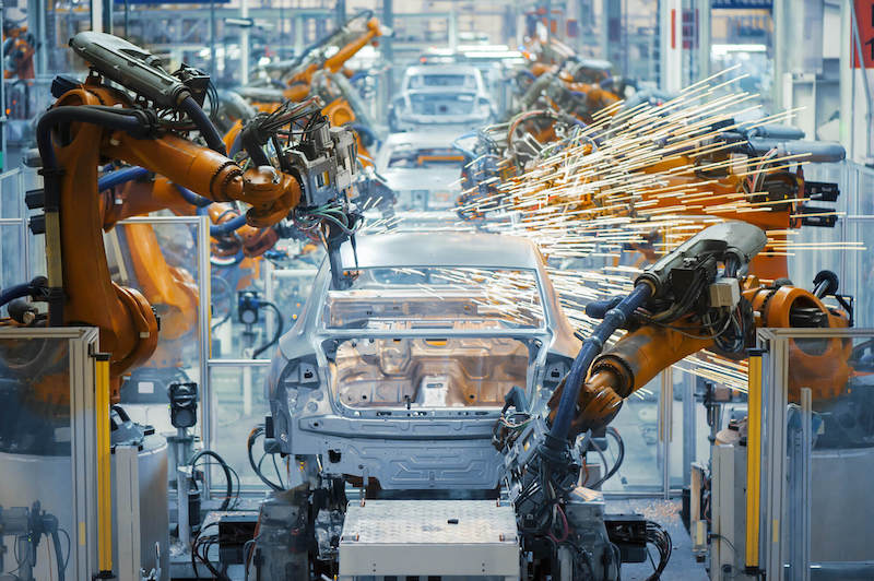 robot arms welding in car assembly line