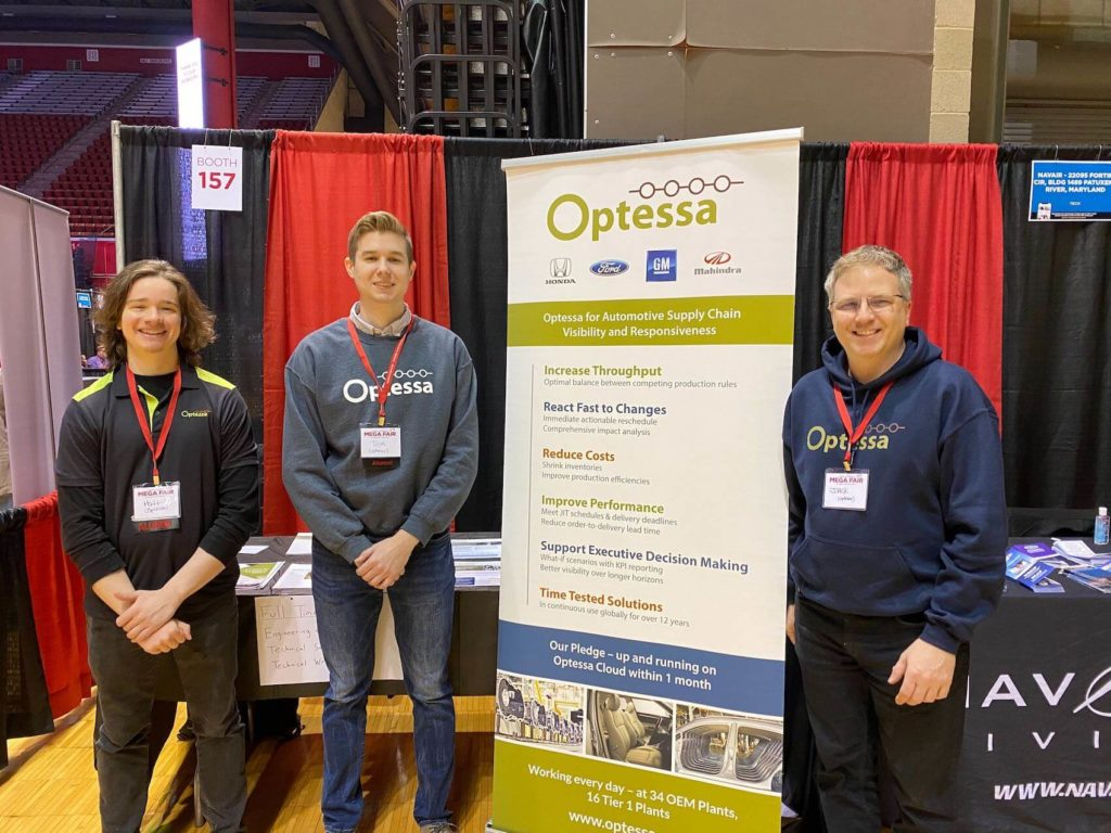 Optessa employees standing in front of tradeshow banner